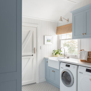 Design ideas for a mid-sized transitional galley utility room in Perth with a farmhouse sink, shaker cabinets, blue cabinets, a side-by-side washer and dryer, white benchtop, white walls, multi-coloured floor and planked wall panelling.