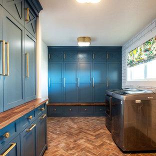 Immagine di una piccola lavanderia multiuso tradizionale con ante in stile shaker, ante blu, top in legno, pareti bianche, pavimento in mattoni, lavatrice e asciugatrice affiancate, pavimento rosso e top marrone