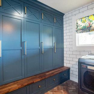 Inredning av ett klassiskt litet brun brunt grovkök, med skåp i shakerstil, blå skåp, träbänkskiva, vita väggar, tegelgolv, en tvättmaskin och torktumlare bredvid varandra och rött golv
