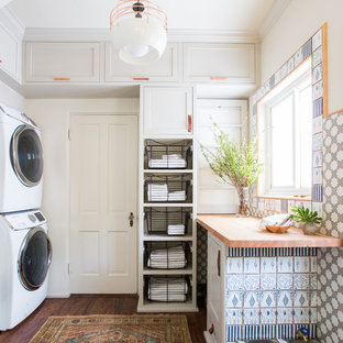 Cette photo montre une buanderie nature de taille moyenne avec un placard à porte shaker, des portes de placard grises, un plan de travail en bois, un mur blanc, un sol en bois foncé, des machines superposées et un plan de travail beige.