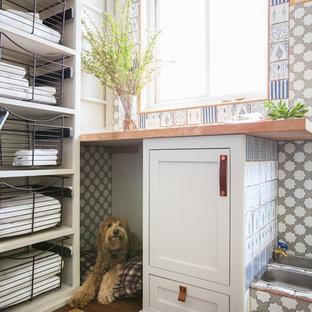 Cette image montre une buanderie marine multi-usage et de taille moyenne avec un placard à porte shaker, des portes de placard grises, un plan de travail en bois, un mur blanc et un sol en bois foncé.