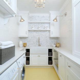 Klassisk inredning av en mellanstor u-formad tvättstuga enbart för tvätt, med en rustik diskho, skåp i shakerstil, vita skåp, vita väggar, en tvättmaskin och torktumlare bredvid varandra, bänkskiva i koppar och målat trägolv