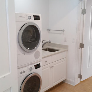 Laundry closet - mid-sized farmhouse single-wall light wood floor and beige floor laundry closet idea in New York with an undermount sink, raised-panel cabinets, white cabinets, laminate countertops, white walls and a stacked washer/dryer