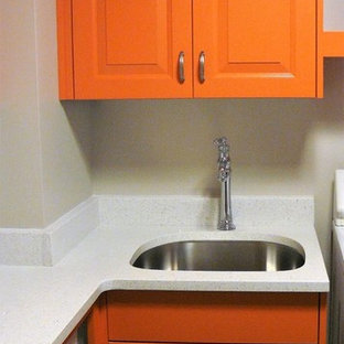Mid-sized contemporary u-shaped dedicated laundry room in Salt Lake City with an undermount sink, raised-panel cabinets, orange cabinets, quartz benchtops, grey walls, porcelain floors, a side-by-side washer and dryer, grey floor and white benchtop.