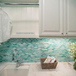 Esempio di una sala lavanderia boho chic di medie dimensioni con lavello sottopiano, ante con bugna sagomata, ante bianche, top in marmo, pareti blu, pavimento in gres porcellanato, lavatrice e asciugatrice a colonna e pavimento beige