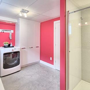 Inspiration för mellanstora moderna linjära grovkök, med rosa väggar, betonggolv och en tvättmaskin och torktumlare bredvid varandra