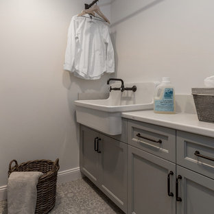 Mid-sized ceramic tile and multicolored floor utility room photo in San Francisco with a drop-in sink, glass-front cabinets, medium tone wood cabinets, quartz countertops, white walls, a side-by-side washer/dryer and white countertops