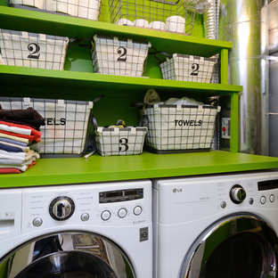 This is an example of an eclectic utility room in New York with open cabinets, green cabinets, green walls, a side by side washer and dryer and green worktops.