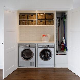 Idéer för små vintage linjära vitt små tvättstugor, med bänkskiva i kvarts, vitt stänkskydd, stänkskydd i tunnelbanekakel, vita väggar, mellanmörkt trägolv, en tvättmaskin och torktumlare bredvid varandra och brunt golv