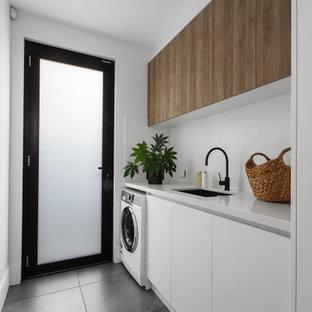 Inredning av en modern vita linjär vitt tvättstuga med garderob, med en undermonterad diskho, släta luckor, vita skåp, vitt stänkskydd, vita väggar och grått golv