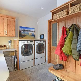 Ispirazione per una lavanderia multiuso american style di medie dimensioni con lavello sottopiano, ante in stile shaker, ante in legno chiaro, top in quarzo composito, pareti bianche, lavatrice e asciugatrice affiancate e pavimento grigio