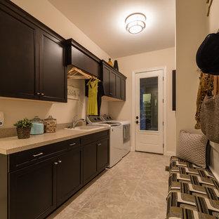Bild på ett mellanstort vintage parallellt grovkök, med en nedsänkt diskho, släta luckor, skåp i mörkt trä, laminatbänkskiva, vita väggar, klinkergolv i keramik och en tvättmaskin och torktumlare bredvid varandra