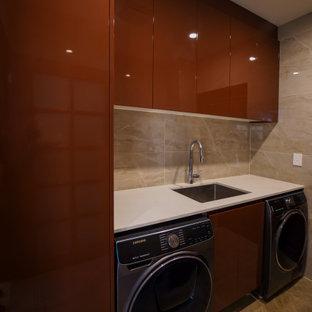 Idéer för att renovera en mellanstor funkis vita parallell vitt tvättstuga enbart för tvätt, med en undermonterad diskho, släta luckor, bruna skåp, bänkskiva i kvarts, beige stänkskydd, stänkskydd i kalk, beige väggar, klinkergolv i keramik, en tvättmaskin och torktumlare bredvid varandra och brunt golv