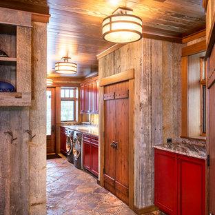 Пример оригинального дизайна: большая прямая универсальная комната в стиле рустика с фасадами с утопленной филенкой, гранитной столешницей, серыми стенами, полом из сланца, со стиральной и сушильной машиной рядом, разноцветным полом, серой столешницей и красными фасадами