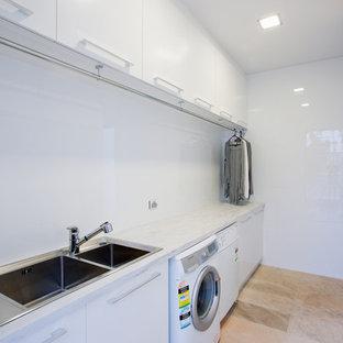 Foto di una lavanderia moderna con lavello a doppia vasca, ante lisce, ante bianche, top in superficie solida, pareti bianche, lavatrice e asciugatrice affiancate e top grigio
