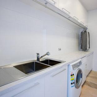 Esempio di una lavanderia minimalista con lavello a doppia vasca, ante lisce, ante bianche, top in superficie solida, pareti bianche, lavatrice e asciugatrice affiancate e top grigio