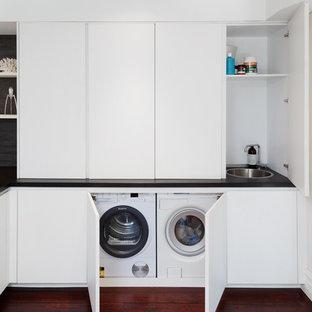 Ispirazione per una lavanderia moderna con lavello a vasca singola, ante bianche, top in granito, pareti bianche, parquet scuro, top nero e lavatrice e asciugatrice nascoste