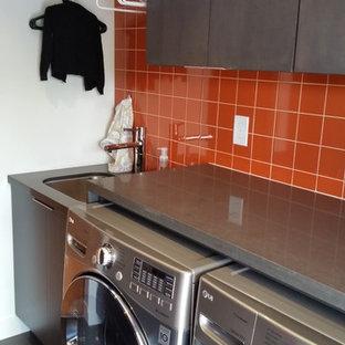 Exemple d'une petit buanderie tendance avec un évier encastré, un placard à porte plane, un plan de travail en quartz, un mur blanc, un sol en bois foncé, des machines côte à côte, un sol noir, un plan de travail gris et des portes de placard grises.