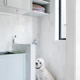 Foto på en stor vintage gula linjär tvättstuga, med en nedsänkt diskho, skåp i ljust trä, bänkskiva i akrylsten, vitt stänkskydd, stänkskydd i porslinskakel, vita väggar, mörkt trägolv, en tvättpelare och brunt golv