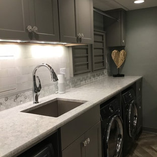 Large shabby-chic style utility room in Milwaukee with a submerged sink, recessed-panel cabinets, grey cabinets, engineered stone countertops, vinyl flooring, a side by side washer and dryer, brown floors and white worktops.