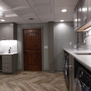 Idee per una grande lavanderia multiuso shabby-chic style con lavello sottopiano, ante con riquadro incassato, ante grigie, top in quarzo composito, pavimento in vinile, lavatrice e asciugatrice affiancate, pavimento marrone e top bianco
