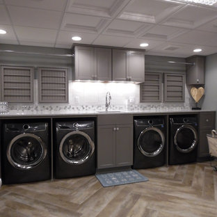 Photo of a large traditional utility room in Milwaukee with an undermount sink, recessed-panel cabinets, grey cabinets, quartz benchtops, vinyl floors, a side-by-side washer and dryer, brown floor and white benchtop.