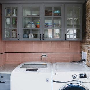 Réalisation d'une buanderie minimaliste en U dédiée et de taille moyenne avec un évier utilitaire, un placard avec porte à panneau surélevé, des portes de placard grises, un plan de travail en quartz modifié, un mur rose, un sol en calcaire, des machines côte à côte, un sol beige et un plan de travail blanc.