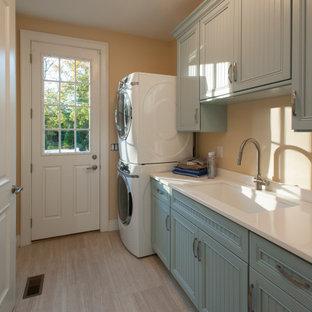 Idéer för att renovera en mellanstor vintage parallell tvättstuga enbart för tvätt, med en undermonterad diskho, turkosa skåp, beige väggar och en tvättpelare