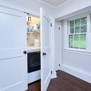 Foto på en liten vintage linjär liten tvättstuga, med vita skåp, vita väggar, mörkt trägolv, en tvättmaskin och torktumlare bredvid varandra och brunt golv