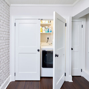 Example of a small transitional single-wall dark wood floor, brown floor, shiplap ceiling and brick wall laundry closet design in Philadelphia with white cabinets, white walls and a side-by-side washer/dryer
