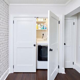 Immagine di un piccolo ripostiglio-lavanderia classico con ante bianche, pareti bianche, parquet scuro, lavatrice e asciugatrice affiancate, pavimento marrone, soffitto in perlinato e pareti in mattoni