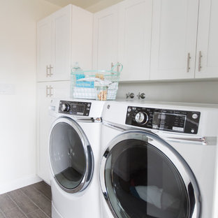 Photo of a mid-sized contemporary single-wall dedicated laundry room in Phoenix with a farmhouse sink, shaker cabinets, white cabinets, quartzite benchtops, white splashback, mosaic tile splashback, ceramic floors, white walls, a side-by-side washer and dryer and brown floor.