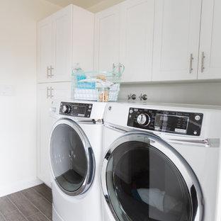 Inspiration för en mellanstor funkis linjär tvättstuga enbart för tvätt, med en rustik diskho, skåp i shakerstil, vita skåp, bänkskiva i kvartsit, vitt stänkskydd, stänkskydd i mosaik, klinkergolv i keramik, vita väggar, en tvättmaskin och torktumlare bredvid varandra och brunt golv