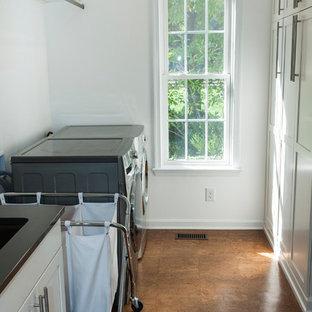Esempio di una lavanderia con ante con riquadro incassato, ante bianche, pareti bianche, pavimento in sughero, lavatrice e asciugatrice affiancate e pavimento marrone