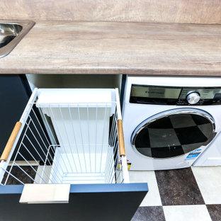 Modern inredning av en liten bruna linjär brunt tvättstuga enbart för tvätt, med en nedsänkt diskho, släta luckor, grå skåp, laminatbänkskiva, bruna väggar, vinylgolv och en tvättmaskin och torktumlare bredvid varandra