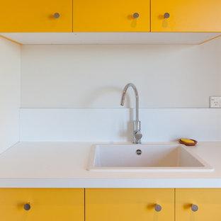 Modern inredning av en mellanstor parallell tvättstuga enbart för tvätt, med gula skåp
