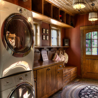 Design ideas for a mid-sized country utility room in Minneapolis with red walls and a stacked washer and dryer.