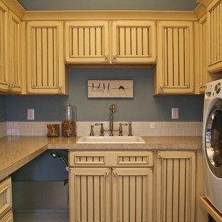 На фото: большая п-образная универсальная комната в классическом стиле с накладной раковиной, фасадами с утопленной филенкой, желтыми фасадами, столешницей из акрилового камня, синими стенами, полом из сланца и со стиральной и сушильной машиной рядом с
