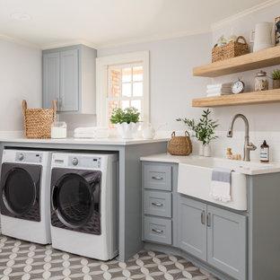 Foto på ett vintage vit linjärt grovkök, med grå väggar, en rustik diskho, skåp i shakerstil, grå skåp, vitt stänkskydd, stänkskydd i tunnelbanekakel, en tvättmaskin och torktumlare bredvid varandra och flerfärgat golv