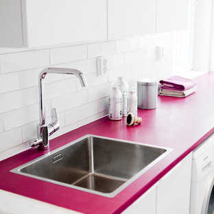 Inspiration for a vintage utility room with a single-bowl sink, flat-panel cabinets, white cabinets, composite countertops, white walls, a side by side washer and dryer and pink worktops.
