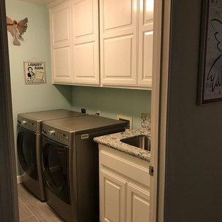 Immagine di una sala lavanderia classica di medie dimensioni con lavello sottopiano, ante con bugna sagomata, ante bianche, top in granito, pareti blu, pavimento in laminato, lavatrice e asciugatrice affiancate e pavimento grigio
