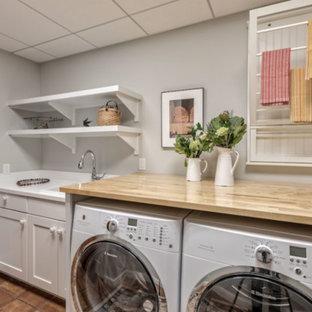 Klassisk inredning av en mellanstor beige linjär beige tvättstuga enbart för tvätt, med grå väggar, en nedsänkt diskho, skåp i shakerstil, grå skåp, träbänkskiva, klinkergolv i terrakotta, en tvättmaskin och torktumlare bredvid varandra och brunt golv