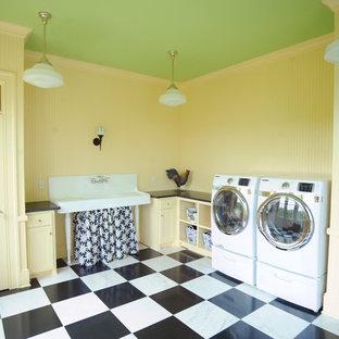Bild på en stor vintage parallell tvättstuga enbart för tvätt, med en rustik diskho, luckor med infälld panel, gula skåp, granitbänkskiva, gula väggar, marmorgolv, en tvättmaskin och torktumlare bredvid varandra och vitt golv