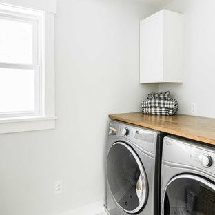 Dedicated laundry room - mid-sized transitional porcelain tile and white floor dedicated laundry room idea in Portland Maine with shaker cabinets, white cabinets, wood countertops, a side-by-side washer/dryer and gray walls