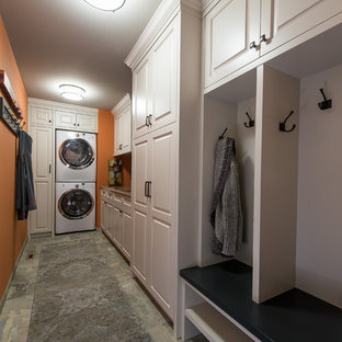 Example of a mid-sized transitional galley slate floor utility room design in Minneapolis with an undermount sink, recessed-panel cabinets, white cabinets, granite countertops, orange walls and a stacked washer/dryer