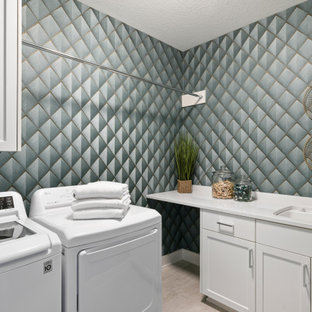 Example of a mid-sized transitional l-shaped ceramic tile, beige floor and wallpaper dedicated laundry room design in Minneapolis with a drop-in sink, white cabinets, green walls, a side-by-side washer/dryer, shaker cabinets and white countertops