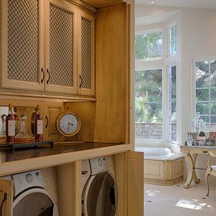 Idee per una grande lavanderia multiuso american style con ante in legno scuro, top in granito, pavimento in pietra calcarea e lavatrice e asciugatrice nascoste