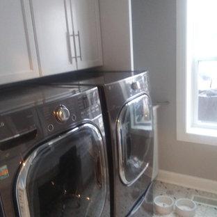 Amerikansk inredning av en mellanstor linjär tvättstuga enbart för tvätt, med luckor med infälld panel, vita skåp, grå väggar, linoleumgolv, en tvättmaskin och torktumlare bredvid varandra och flerfärgat golv