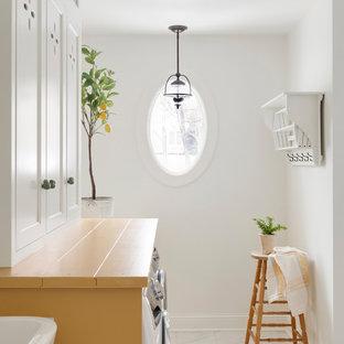 Idéer för ett mellanstort lantligt gul linjärt grovkök, med en nedsänkt diskho, luckor med profilerade fronter, gula skåp, en tvättmaskin och torktumlare bredvid varandra och vitt golv