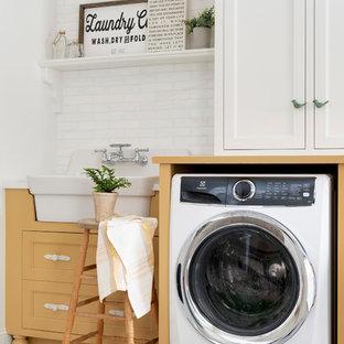 Idee per una lavanderia multiuso country di medie dimensioni con lavello da incasso, ante a filo, ante gialle, lavatrice e asciugatrice affiancate, pavimento bianco e top giallo